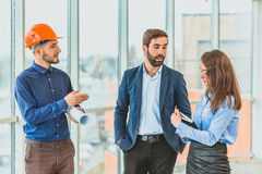 A group of beautiful business partners in diving. Discussing the plan, the architect stands in cashier. Discussing the case and smiles at his colleagues while royalty free stock image