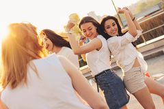 Group of beautiful carefree girlfriends dancing have fun in the city street parking on the background of evening sunset. Group of beautiful carefree girlfriends royalty free stock images