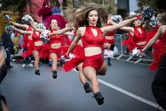 Group of beautiful cheerleaders from lithuania. ITALY, SANREMO - march 11, 2018 :group of beautiful cheerleaders from lithuania in red  costume dancing along the Stock Photography