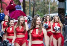 Group of beautiful cheerleaders from lithuania smiling. ITALY, SANREMO - march 11, 2018 :group of beautiful cheerleaders from lithuania in red  costume walking Royalty Free Stock Images