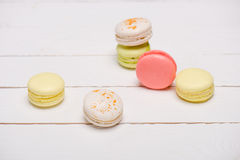 Group of beautiful colorful macarons on white wooden table royalty free stock photography
