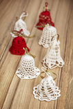 Group of beautiful crochet christmas bells on the wooden texture Stock Image