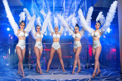 Group of beautiful female dancers in white carnival costumes. Full length shot of five gorgeous women dancing wearing white carnival outfits nightclub festival Royalty Free Stock Photo