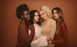 Group of beautiful female friends standing together. On brown background. Multi ethnic women in studio looking at camera Royalty Free Stock Images