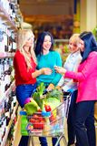 Group of beautiful girls choosing wine in supermarket Royalty Free Stock Photo