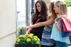 Group of beautiful girls looking at the shop window. Stock Photo