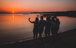 Group of beautiful people having fun at sunset beach(selfie) royalty free stock photo
