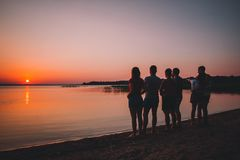Group of beautiful people having fun at sunset beach stock images