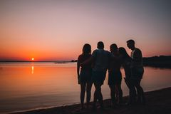 Group of beautiful people having fun at sunset beach royalty free stock photography