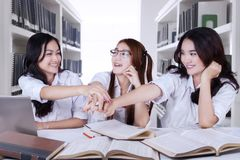 Beautiful high school students joining hands together. Group of beautiful high school students joining hands together before studying in the library Royalty Free Stock Image
