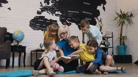 Group of beautiful kids talking about book with nursery teacher in preschool. Happy child day care worker with children. Reading a book in elementary school or stock footage