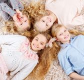 Group of beautiful little girls lying head to head. Royalty Free Stock Photo