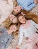 Group of beautiful little girls lying head to head. Stock Photo