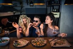 Group of beautiful people sits together and eats food with wine stock photo