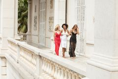 Group of beautiful ladies in elegant dresses at sunny summe. Group of beautiful ladies wearing elegant dresses. Girls having fun together, smiling. Two blonde royalty free stock photo