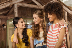 Group of beautiful smiling young women standing embracing on porch. Multiethnic group of beautiful smiling young women standing embracing on porch Royalty Free Stock Photo