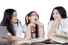 Group of beautiful student laughing while studying Stock Image