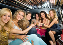Group of beautiful women. Clinking glasses with champagne inside a limousine Stock Photo