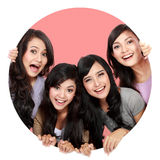 Group of beautiful women smiling peeping through circle hole Stock Photography