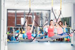 Group of beautiful young women doing exercise on TRX.  stock photo