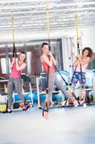 Group of beautiful young women doing exercise on TRX.  royalty free stock images
