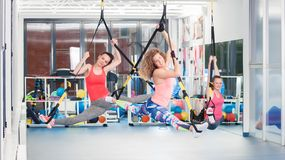 Group of beautiful young women doing exercise on TRX.  royalty free stock photo