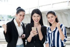 group of beautiful young women friends using a smart phone and laughing .three girl exciting business online of news stock photos