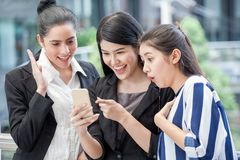 group of beautiful young women friends using a smart phone and laughing outdoors .three girl exciting business online of news royalty free stock photography