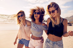 Group of beautiful young women strolling on a beach. Three friends walking on the beach and laughing on a summer day, enjoying vacation royalty free stock images