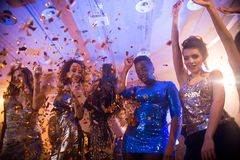 Young People Enjoying Raving Party. Group  of beautiful young women wearing glittering dresses dancing under golden confetti shower enjoying raving party in Stock Image