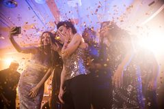 Girls Taking Selfie at Awesome Party. Group of beautiful young women wearing glittering dresses dancing under golden confetti and taking selfies enjoying raving royalty free stock image