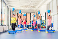 Group of beautiful young women working out on blue stepper. Group of beautiful young women working out on blue stepper and smiling stock photos