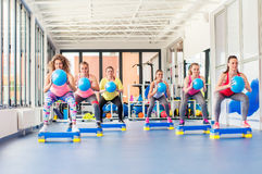 Group of beautiful young women working out on blue stepper. Group of beautiful young women working out on blue stepper and smiling stock photo