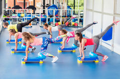 Group of beautiful young women working out on blue stepper. Group of beautiful young women working out on blue stepper and smiling royalty free stock photo