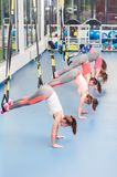 Group of beautiful young women working out on TRX.  royalty free stock photography