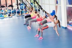 Group of beautiful young women working out on TRX.  royalty free stock photo