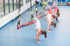 Group of beautiful young women working out on TRX.  stock photos