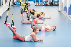 Group of beautiful young women working out on TRX. Resting time.  royalty free stock photos