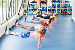 Group of beautiful young women working out on TRX. Group of beautiful young women working out on TRX and smiling stock photo