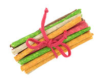 Group of beef hide dyed dog snacks tied with cord. Top view of a group of dyed beef hide dog treats tied with a knotted red cord isolated on a white background Stock Images