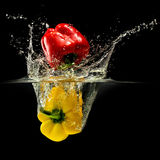 Group of bell pepper falling in water with splash on black background Stock Photography