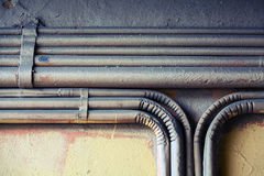 Group of bent vintage electrical conduits. Abstract industrial background, group of bent vintage electrical conduits mounted on a concrete wall. Old style toned stock photos