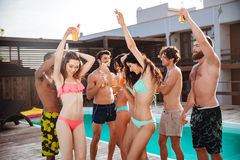 Group of best friends having fun dancing at swimming pool Stock Photography