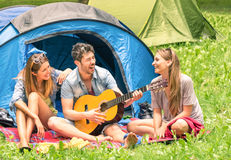Group of best friends singing and having fun camping outdoors. Group of best friends singing and having fun camping together - Concept of carefree youth and Royalty Free Stock Photo