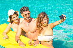 Group of best friends taking selfie at the swimming pool. With yellow airbed - Concept of friendship in the summer with new trends and technology - Young men Stock Images