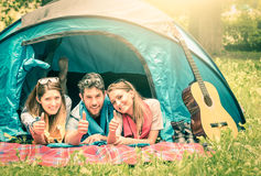 Group of best friends with thumbs up in camping  tent. Group of best friends with thumbs up having fun camping together - Concept of carefree youth and freedom Royalty Free Stock Photography