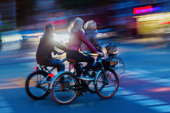 Group of bicycle riders at night. Group of bicycle riders on a city street at night Stock Image