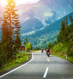 Group of bikers in Alps. Active vacation, curve road in the mountains, fresh pine trees along highway, bright sunshine, extreme transportation Royalty Free Stock Photo