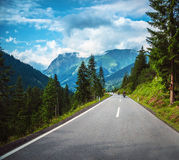 Group of bikers in mountains. Group of bikers riding on road pass along Alpine mountains, travelers in Europe, mountainous highway, pine tree forest, extreme Stock Image