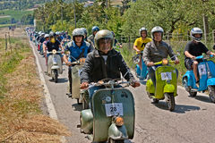 Group of bikers riding vintage italian scooters Vespa and Lambre. Tta in motorcycle rally `8th Vespa Raduno` on June 3, 2012 in Gorolo di Borghi, FC, Italy Stock Photos